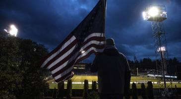 Photo taken behind a man holding an American flag looking down at a lit sportsfield at night