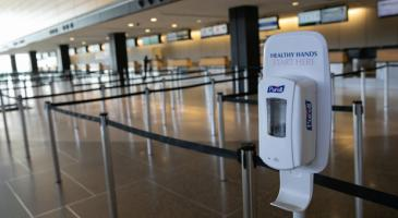 Photo of empty airport check-in lines with hand sanitizer dispenser stand at front