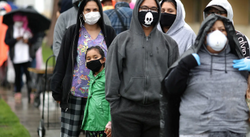 People wait in line outside food bank, wearing protective masks