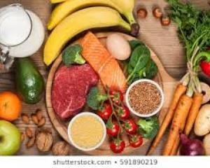 Array of fruits, raw vegetables, meat and mile on wooden surface